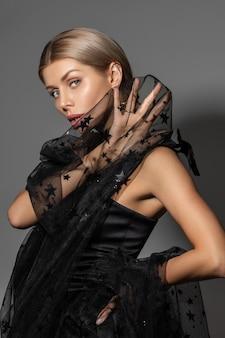Portret van stijlvolle mooie vrouw in zwarte jurk staan en kijken naar camera, op grijs