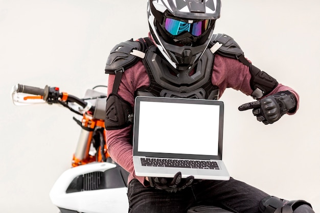 Portret van stijlvolle motorrijder met laptop