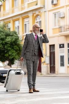 Portret van stijlvolle senior man die aan de telefoon spreekt