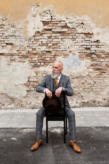 Portret van stijlvolle senior man die buiten zit