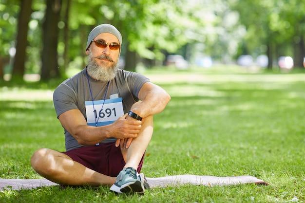 Portret van stijlvolle senior man met baard op gezicht deelnemen aan zomer marathon zittend ontspannen op gras