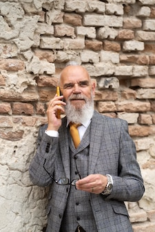 Portret van stijlvolle senior man op zijn telefoon