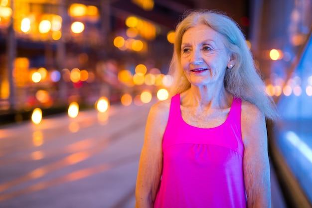 Portret van stijlvolle senior vrouw buiten 's nachts