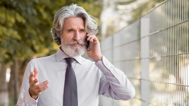 Portret van stijlvolle volwassen man praten aan de telefoon