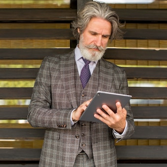 Portret van stijlvolle volwassen mannelijke browsen tablet Premium Foto