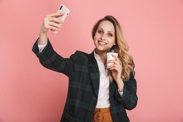 Portret van stijlvolle vrouw 30s in trendy jas met behulp van mobiele telefoon en het drinken van afhaalmaaltijden koffie geïsoleerd op roze