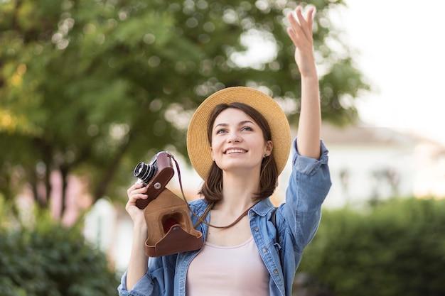 Portret van stijlvolle vrouw met hoed en camera