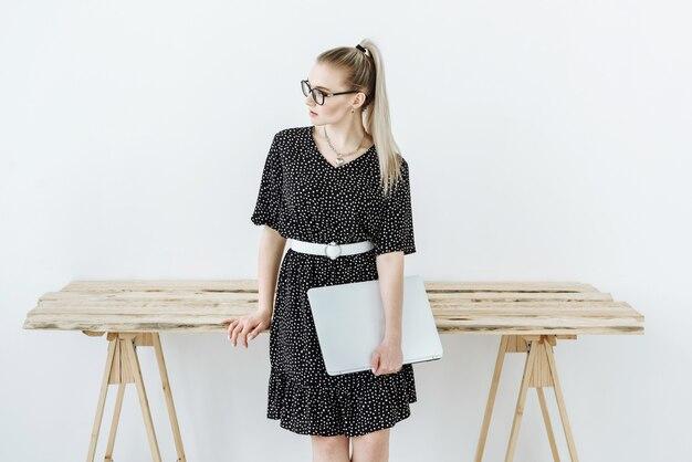Portret van stijlvolle vrouw met laptop in bril en jurk in de buurt van tafel op witte scène