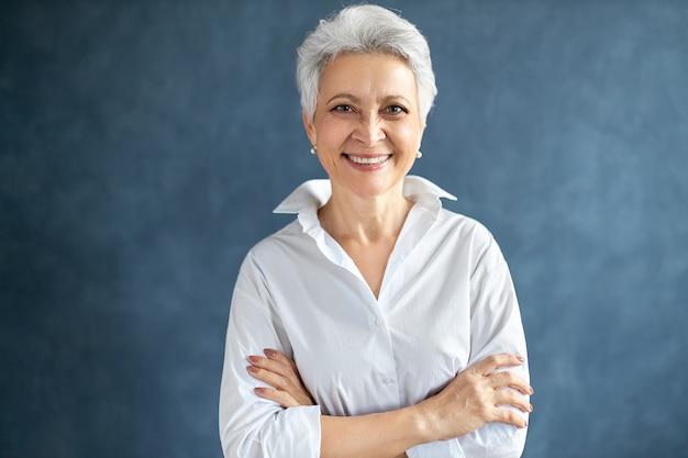 Portret van stijlvolle vrouwelijke eventmanager van middelbare leeftijd die wit formeel overhemd draagt dat geïsoleerd stelt die wapens op haar borst houdt