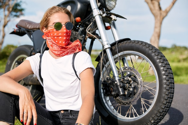 Portret van stijlvolle vrouwelijke fietser draagt bandana en zonnebril, zit in de buurt van snelle motor, kijkt peinzend weg, heeft rust in de open lucht na een lange rit, geniet van vrijheid en hoge snelheid. hobby concept