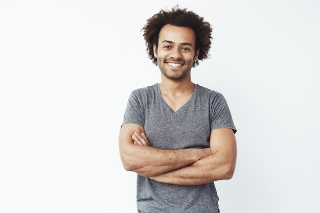 Portret van stong en knappe afrikaanse mannelijke student die met gekruiste wapens over witte muur glimlachen. binnenkort startende eigenaar of verkoper.
