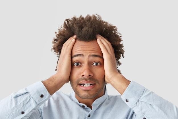 Portret van stressvolle gekrulde man raakt hoofd, lijdt aan hoofdpijn, ziet er stressvol uit