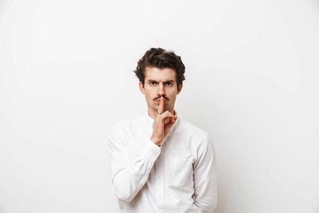 Portret van strikte besnorde man met shirt met vinger op zijn lippen geïsoleerd op wit