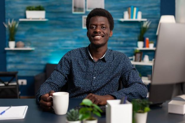 Portret van student die lacht terwijl hij in de camera kijkt