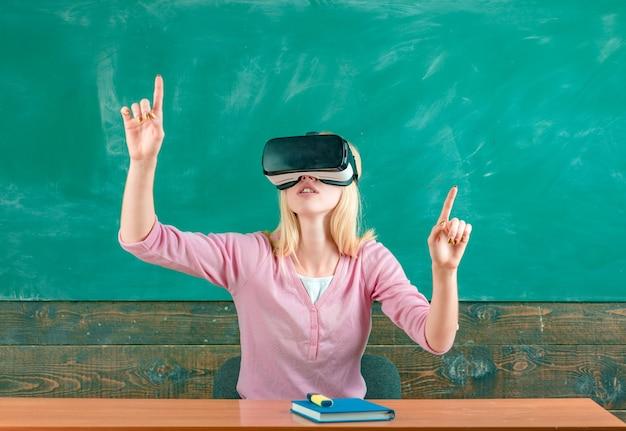 Portret van student hef armen op en draag een vr-headset. student klaar voor vr-ervaring. vrouw zit aan bureau met laptop en zet een virtual reality-bril op. vr-technologie in het onderwijs.