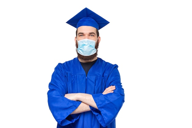 Portret van student man met bachelor diploma kleding met gekruiste armen en gezichtsmasker
