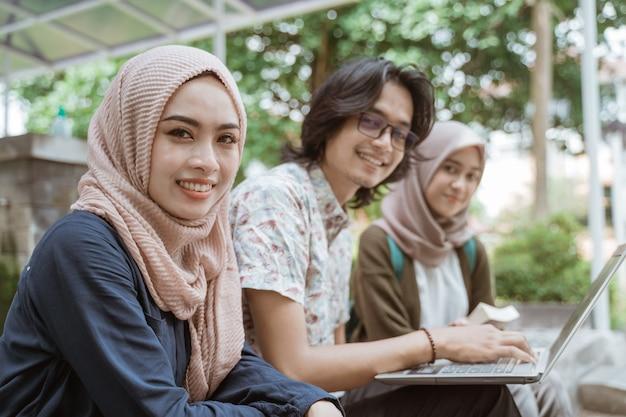Portret van studenten die een camera samen met laptop op het terrein van de campus bekijken