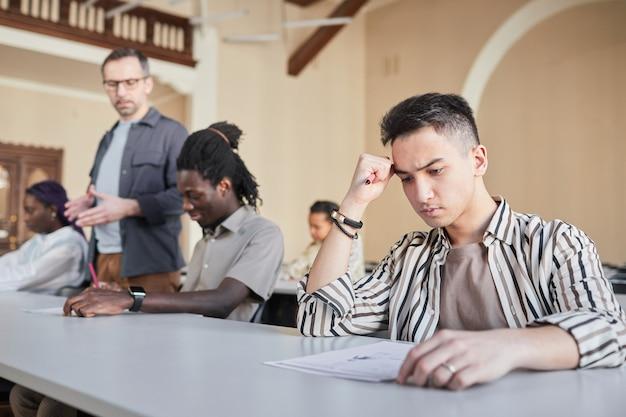 Portret van studenten die examen afleggen terwijl ze aan een bureau in het auditorium zitten, focus op jonge aziatische man die op de voorgrond denkt, kopieer ruimte