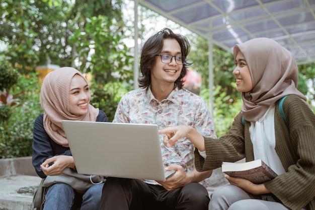Portret van studenten die samen met laptop op de campuswerf bespreken.