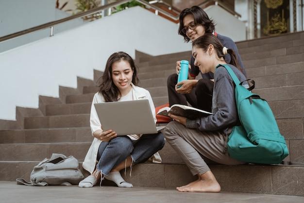 Portret van studenten zitten in groepjes te werken op de campus van de vloertrap