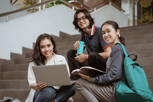 Portret van studenten zitten werken in groepen camera kijken op de vloer trap campus