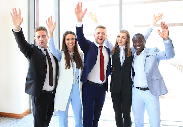 Portret van succesvolle bedrijfsgroep die handen zwaait in kantoor