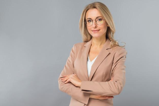 Portret van succesvolle blonde jonge vrouw met gekruiste wapens die zich tegen grijze achtergrond bevinden