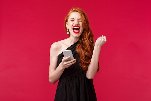 Portret van succesvolle en tevreden, gelukkige roodharige meid die wint, ontvangt geweldig nieuws via bericht, geschenkpomp als kampioen, schreeuw ja, ze deed het, zegevierend in zwarte elegante jurk, rode muur