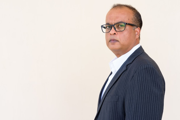 Portret van succesvolle indiase zakenman tegen gewone muur buitenshuis