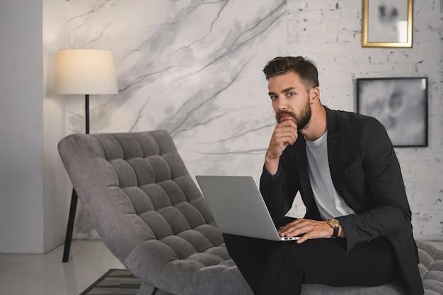 Portret van succesvolle jonge ongeschoren zakenman in elegante formele jas op afstand werken op laptop, met behulp van gratis draadloos internet in luxe hotelsuite terwijl ze op zakenreis