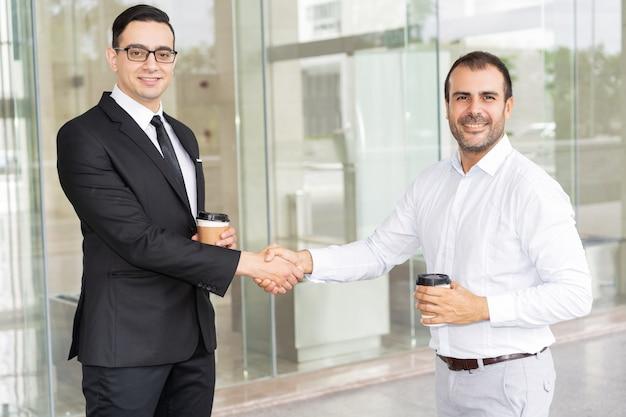Portret van succesvolle medio volwassen partners die handen schudden