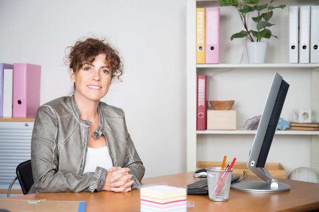 Portret van succesvolle midden oude onderneemster die op haar kantoor werkt