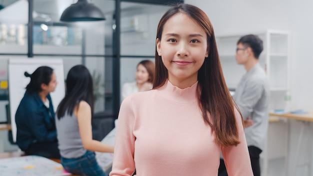 Portret van succesvolle, mooie zakenvrouw slimme vrijetijdskleding die naar de camera kijkt en glimlacht Gratis Foto