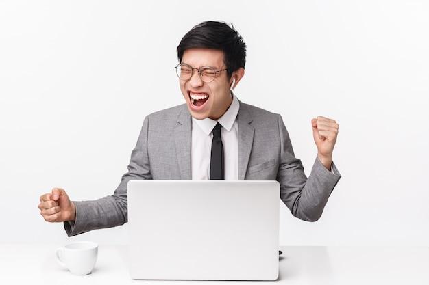 Portret van succesvolle tevreden jonge aziatische man in grijs pak, draadloze koptelefoon, ogen dicht zeggen ja, schreeuwen van plezier en vreugde, zegevieren geweldige e-mail ontvangen, zitten in de buurt van laptop