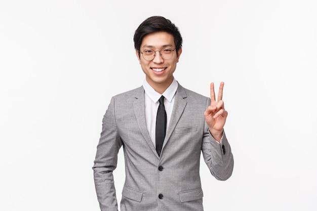 Portret van succesvolle vastberaden en zelfverzekerde jonge aziatische man gevoel dat hij de deal voor onderneming kan krijgen, permanent in grijs pak, vredesteken tonen en glimlachen, staande op witte muur