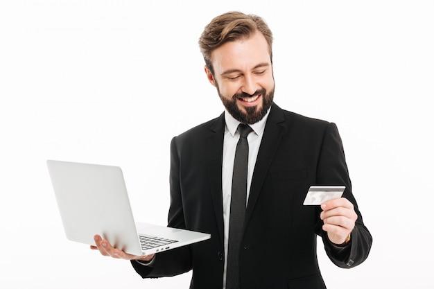 Portret van succesvolle zakenman die en laptop en plastic creditcard in handen glimlacht houdt, dat over witte muur wordt geïsoleerd