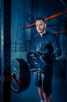 Portret van super fit gespierde jonge man trainen in de sportschool met barbell