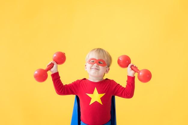 Portret van superheld kind. super held kind tegen gele papieren achtergrond. gelukkig kind met rood masker en cape van superheld. kinderen dromen en verbeeldingsconcept