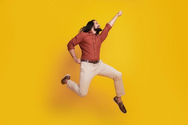 Portret van superheld man springen verhogen vuist vliegen wereld redden op gele achtergrond
