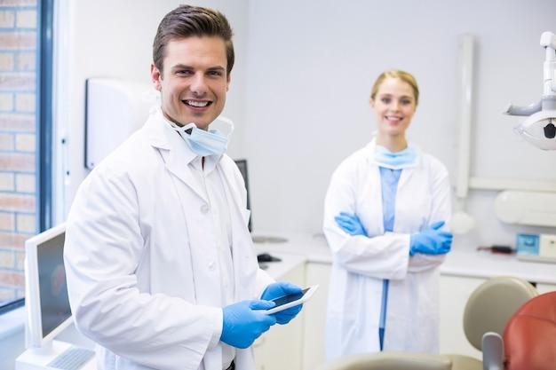 Portret van tandarts die digitale tablet met zijn collega houdt