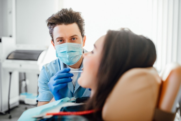 Portret van tandarts in blauw masker die met geduldige tanden in moderne kliniek werkt.