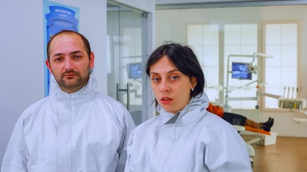 Portret van teamarts in de tandartspraktijk die beschermende maskers opstijgt die op de camera kijken met vlekken op het gezicht met een pbm-pak in de wachtkamer. concept van nieuwe normale kliniek bij uitbraak van coronavirus