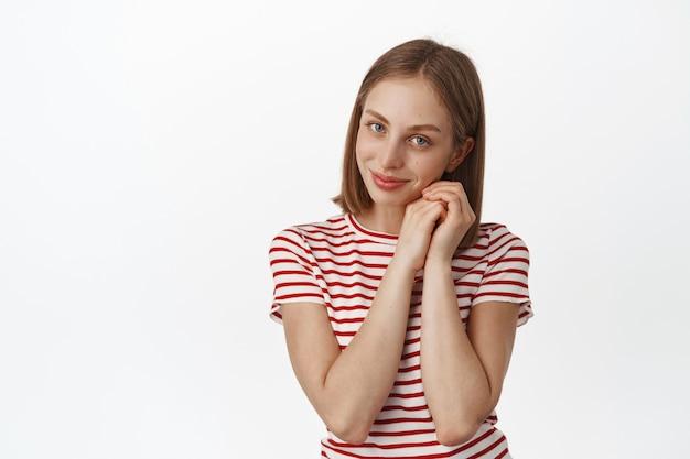 Portret van tedere en mooie jonge vrouw met blond haar, geen make-up schoon gezicht, bewonder smth, koket en mooi aan de voorkant, dromend, staand in t-shirt tegen witte muur.