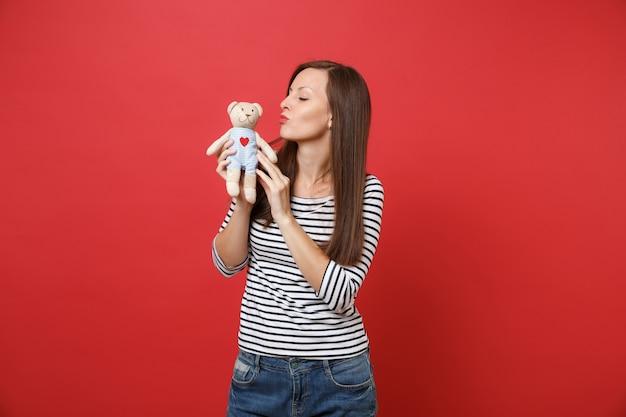 Portret van tedere jonge vrouw die kusjes blaast en luchtkus stuurt naar teddybeer knuffel in handen