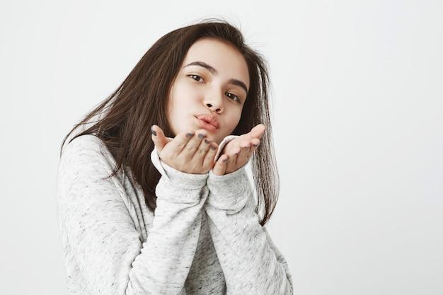 Portret van tedere mooie jonge vrouw die kussen verzendt en het met gebaar toont
