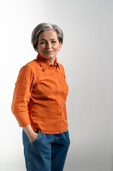 Portret van tedere rijpe vrouw die glazen draagt die voorzijde in oranje overhemd en denimbroek bekijken
