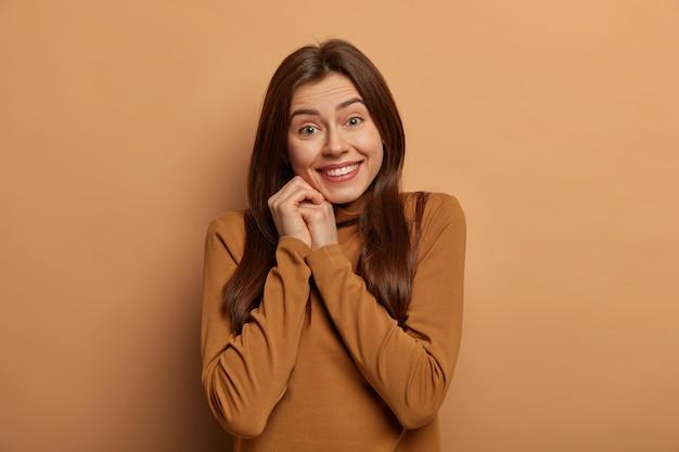 Portret van tedere vrouw glimlacht breed, heeft witte tanden, geniet van een aangenaam moment, draagt coltrui, geïsoleerd over bruine ruimte