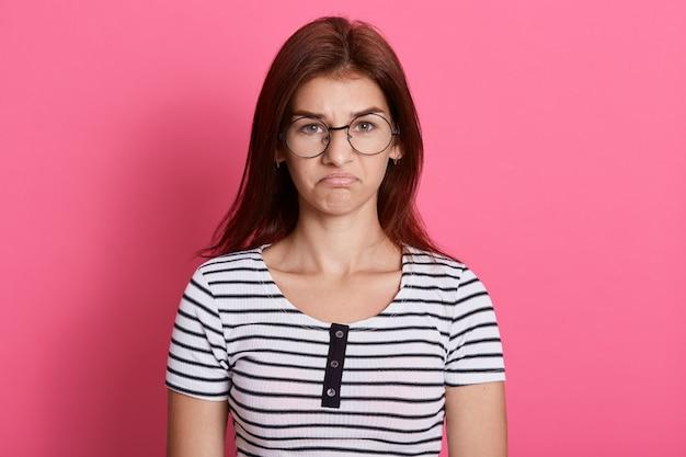 Portret van teleurgesteld schattig meisje, gekleed in een gestreepte casual t-shirt met een verstoorde gelaatsuitdrukking, poseren geïsoleerd over roze muur.