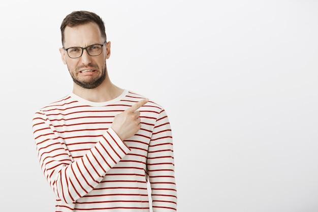 Portret van teleurgestelde grappige blanke man die antipathie toont terwijl hij naar de rechterbovenhoek wijst