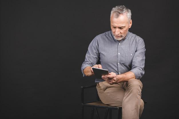 Portret van teruggetrokken hogere mensenholding in zijn hand een digitale tablet terwijl zitten, die glazen houden.